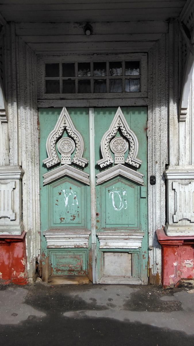 Створки дверей в нижней части касаются асфальта. Ручек нет.