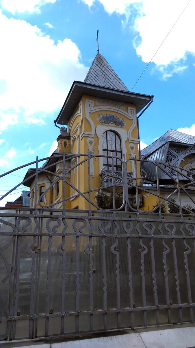 Фасады особняка украшены выделяющимся на желтом фоне гладких стен лепным растительным орнаментом, огромными окнами и тремя майоликовыми панно с пейзажами.