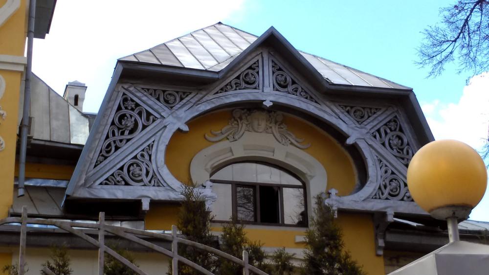 Очень красива резная «решетка», как-бы продолжающая «мансардную» крышу и обрамляющая окно второго этажа с маскароном над ним.