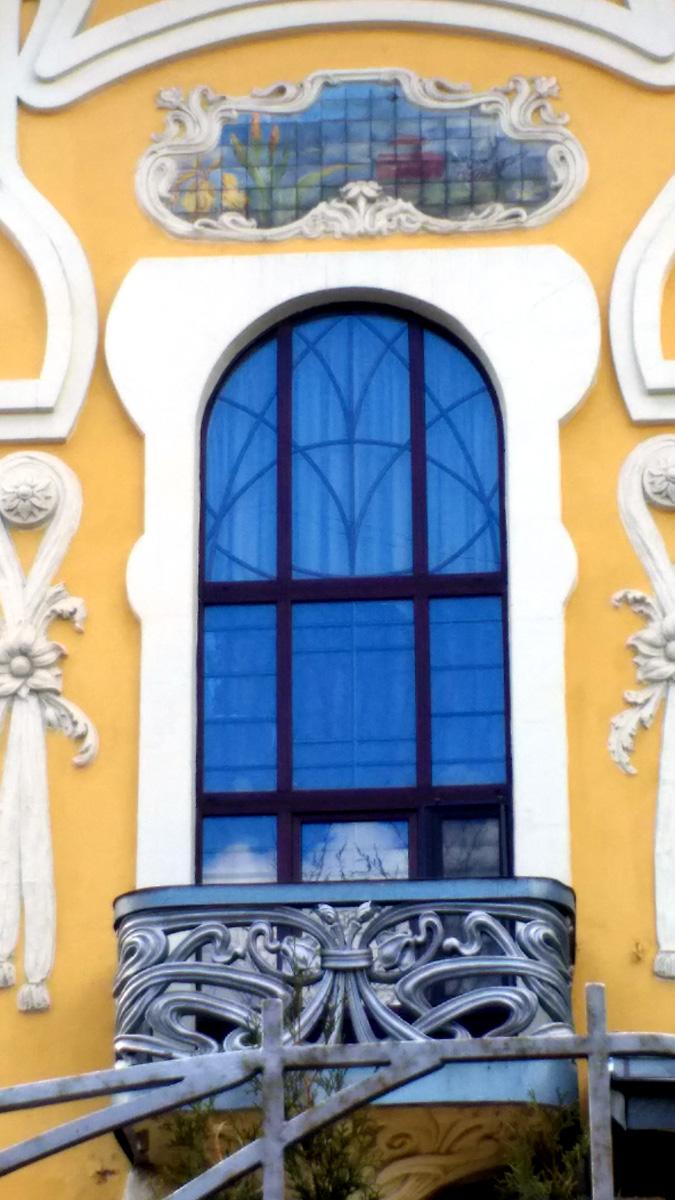 Панно расположено над вытянутым по вертикали окном башенки над юго-восточным углом здания и изображает распускающиеся на закате желтые крокусы и парящую над полем птичку с красной грудкой на фоне лазурного неба и восходящего из-за горизонта и перерезанного узкой полоской облаков рдяного солнечного диска.