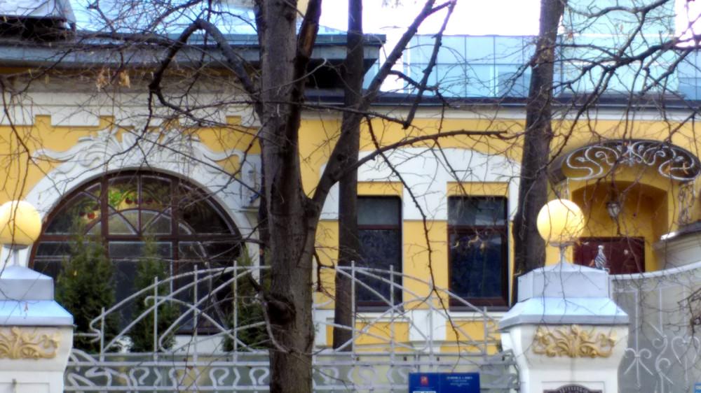 Огромное окно первого этажа украшают растительные витражи.