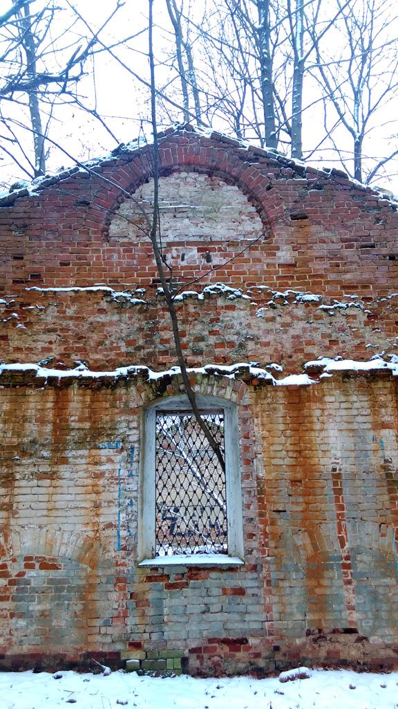 Окно чердака заложено кирпичами. С двух сторон от окна в кирпичной кладке выложены арки. Интересно, для чего?