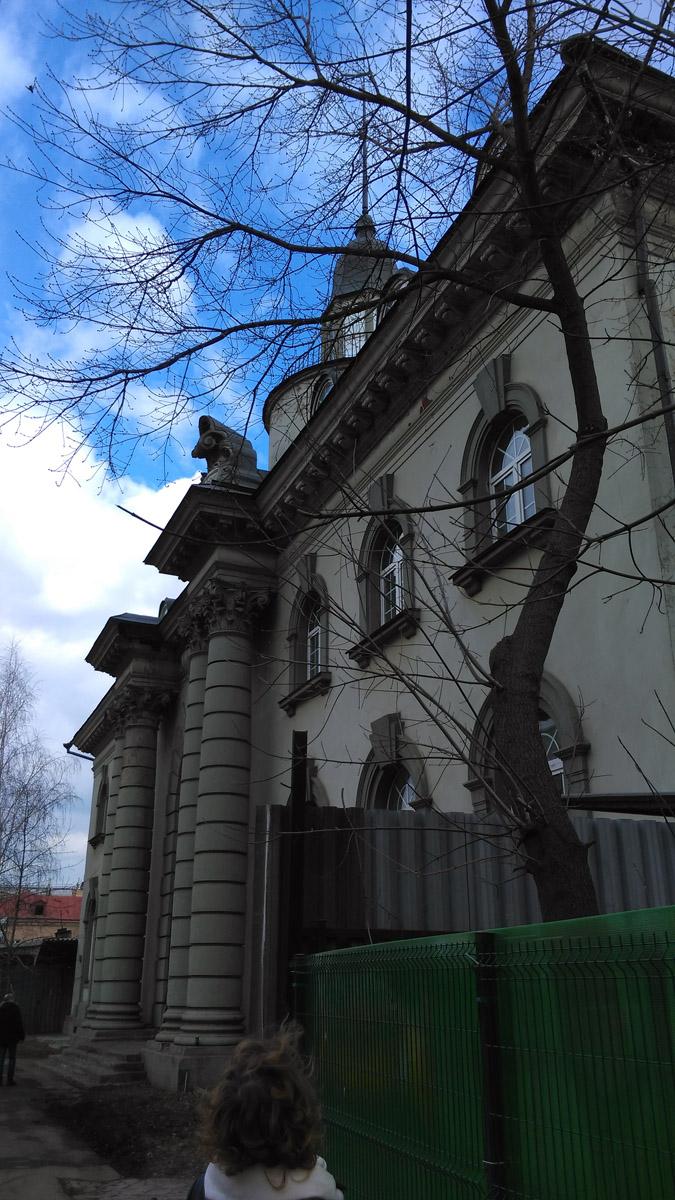 Если посмотреть на здание сбоку, то с определенного ракурса герб с инициалами на фоне синего неба становится похожим на конскую голову.