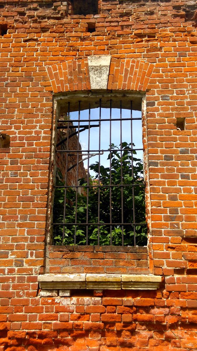 Сквозь окно видны железные опоры внутреннего балкончика.