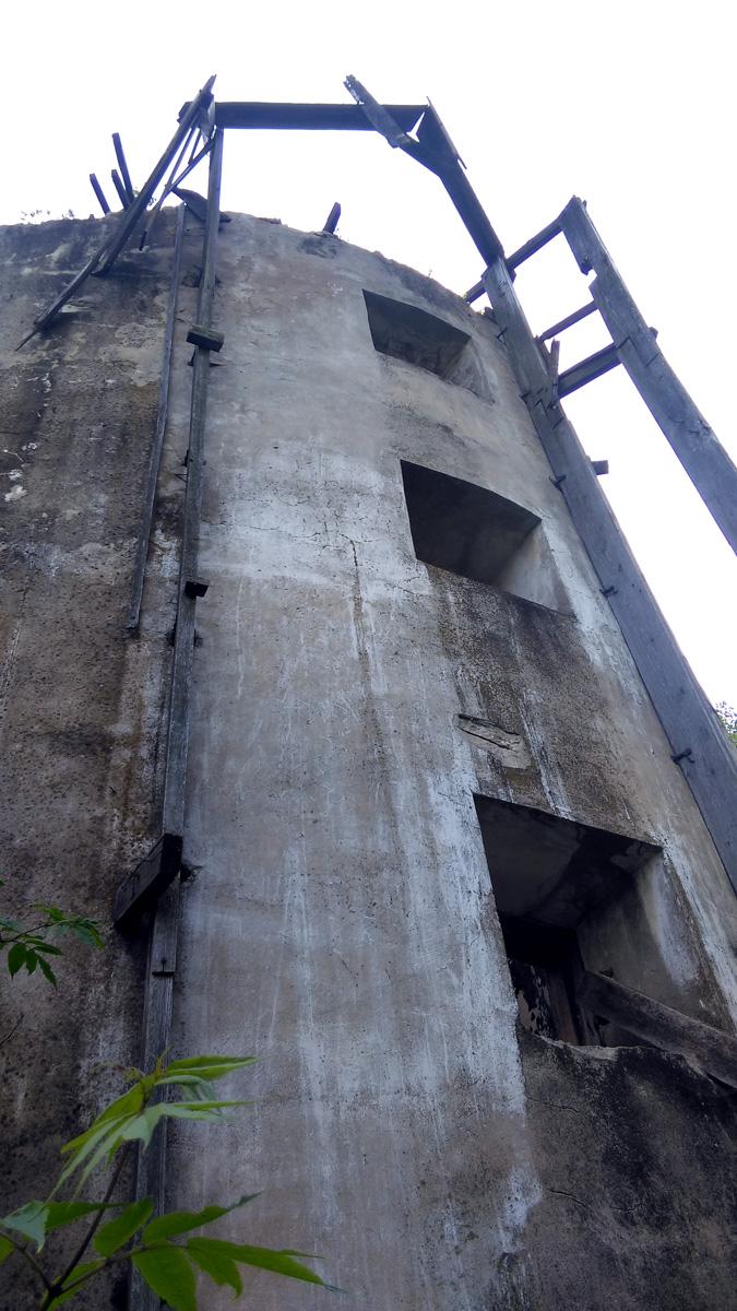 Деревянная конструкция на стене разрушена и куча досок валяется в высокой траве рядом. Внутри голые стены и доски плавающие в луже. Пора домой.