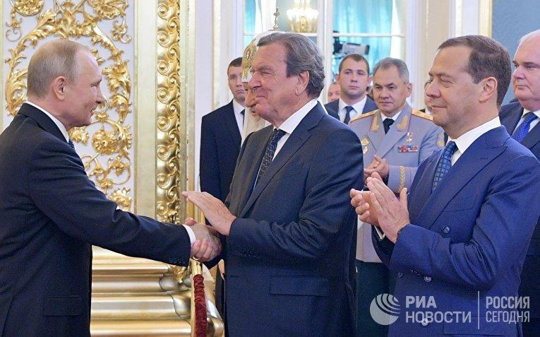 7 мая 2018. Избранный президент РФ Владимир Путин, председатель правительства РФ Дмитрий Медведев и экс-канцлер Германии Герхард Шредер (в центре) во время церемонии инаугурации в Кремле.