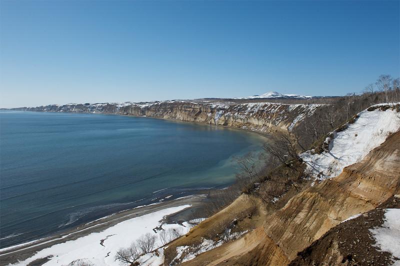 Вид на вулкан Головнина (вдали справа) и Головнинский клиф с мыса Пузанова. Автор фото: Пётр Романов.