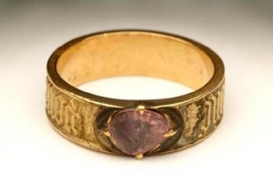 Gold ring, set with a purple spinel in a claw setting. There is an inscription around the sides.