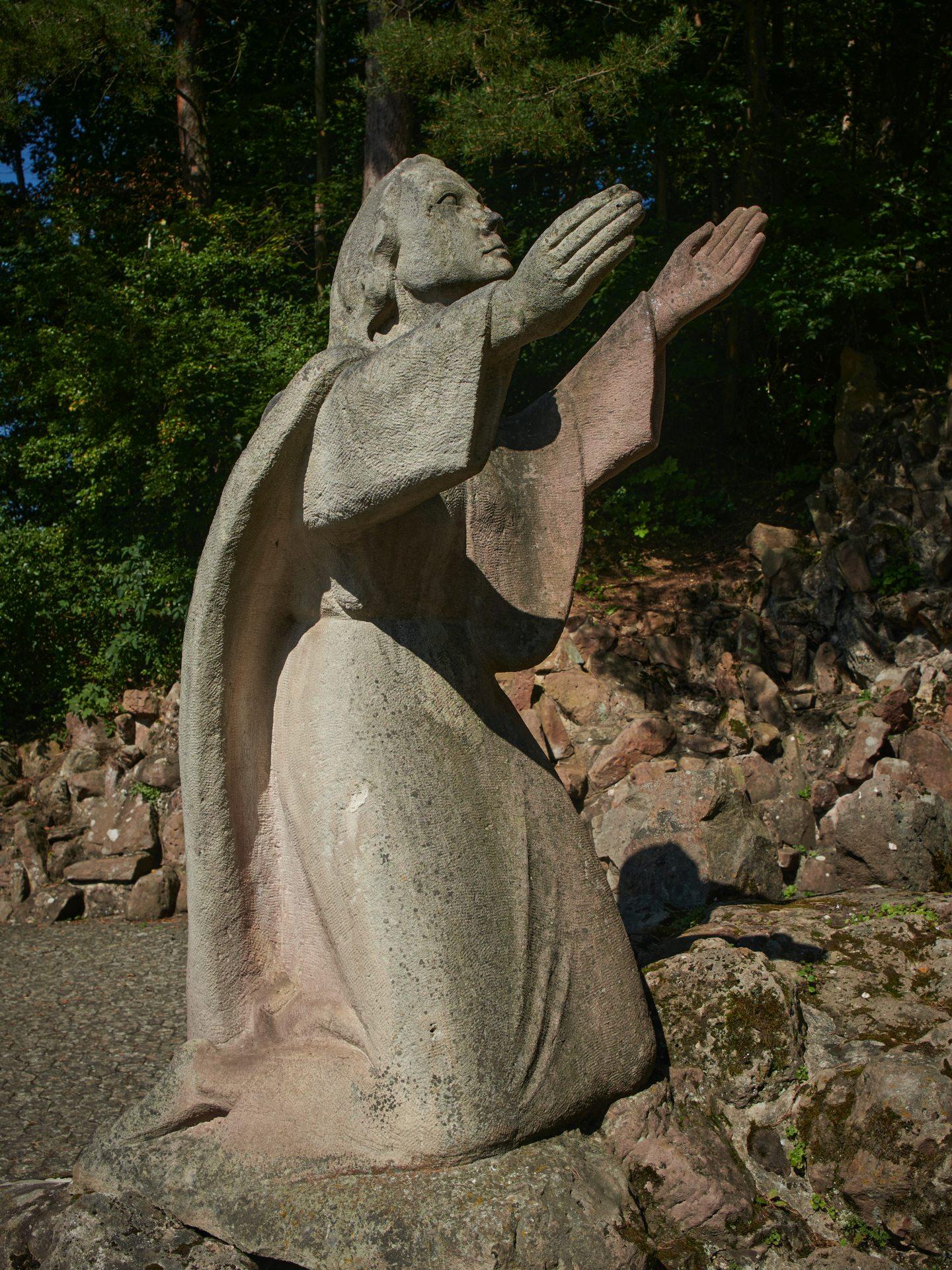 Die Heilige Bernadette. Eine demütige Geste, die mir unangenehm ist. Eine Religion, die eine solche Unterwerfung goutiert, soll mir zu einem besseren Leben verhelfen?