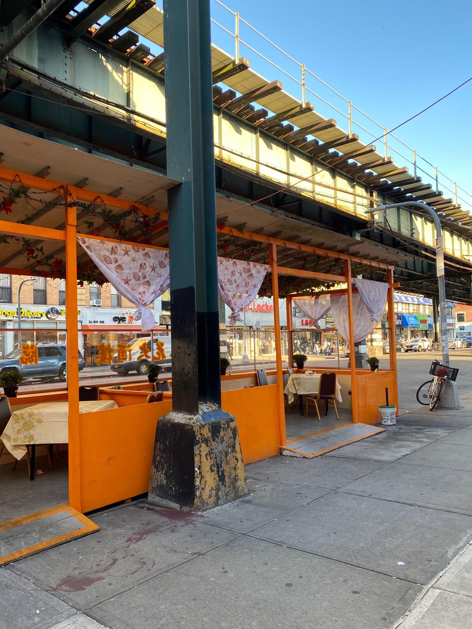 Выносные столики от ресторана на улице под трейном.На проезжей части.