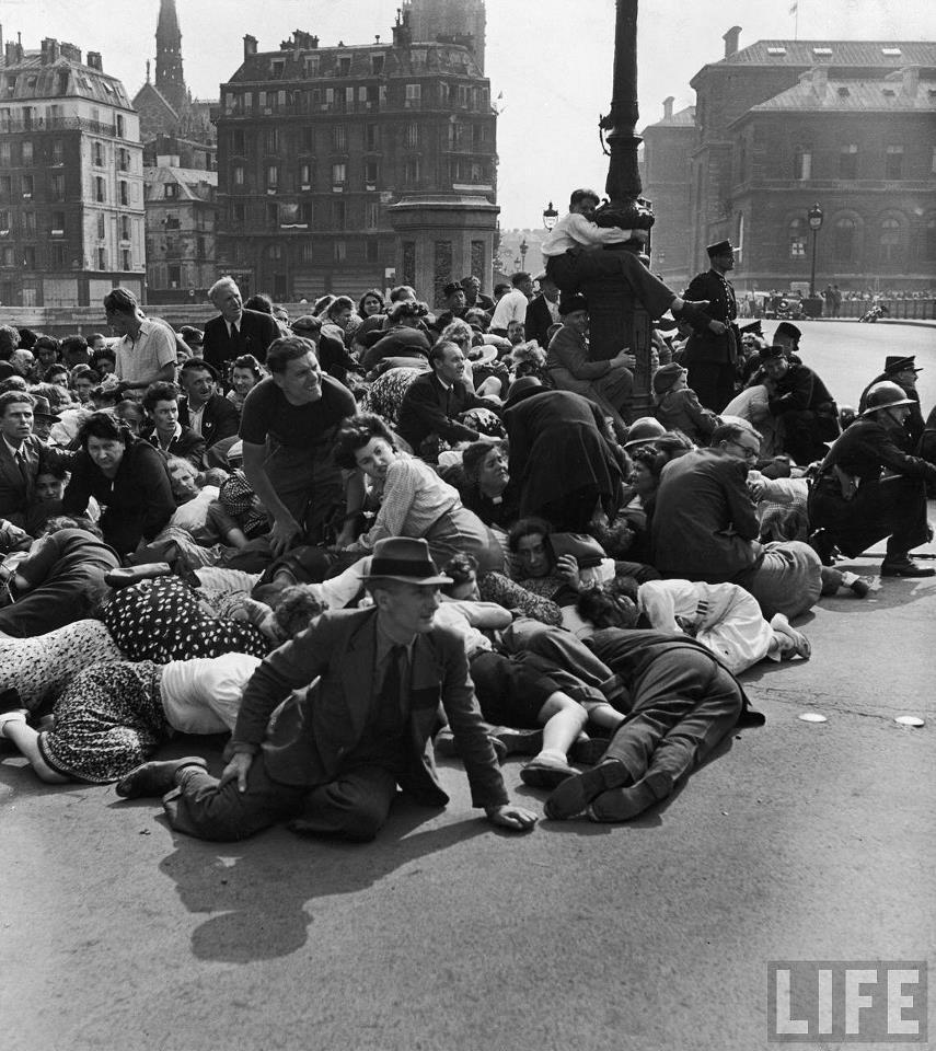 en septembre 1944 sur le pont d'Arcole, où les Parisiens essayent de se protéger contre le feu des derniers Allemands dans la ville... (photo de Frank Scherschel pour Life Magazine)