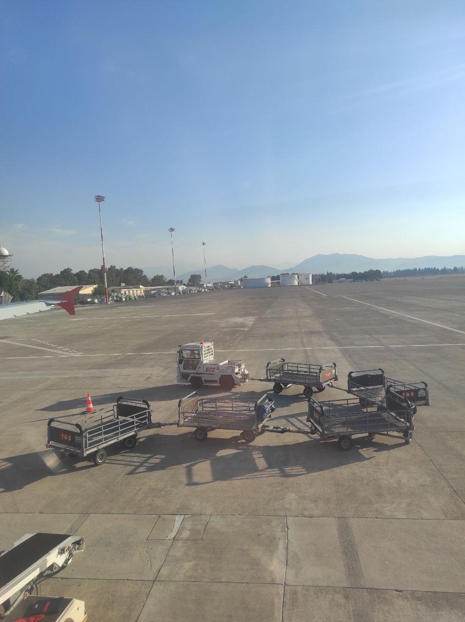 """Тележки, на которых везли багаж, привязались """"паровозиком"""" и отъезжают от самолёта"""