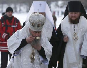 Православный священник, епископ Онуфрий, пьет Святую, Крещенскую воду