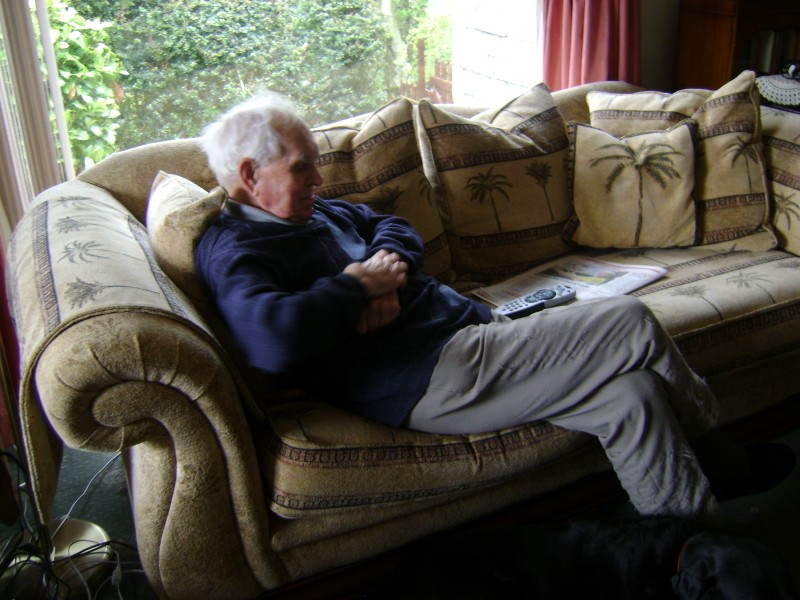 Dad with Cooper at his feet, relaxing in his living room at Robin Hill.