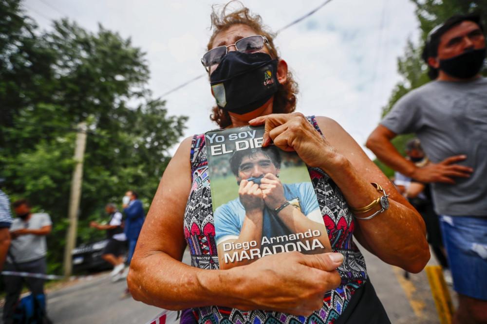 Женщина держит биографию Диего Марадоны возле его дома в Буэнос-Айресе, Аргентина. Фото: AP