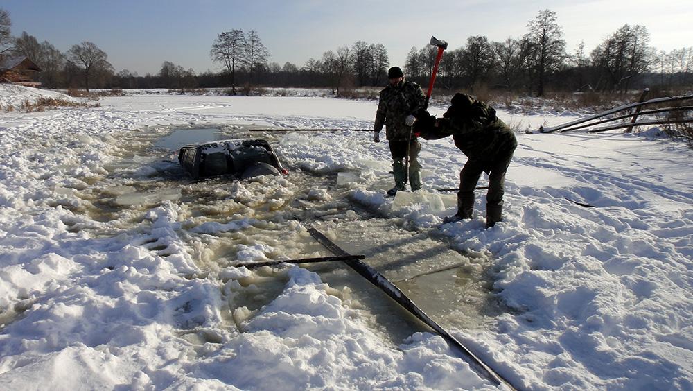 Ребята ломают лед, чтобы вытащить машину.