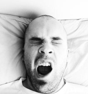 A bald man yawning