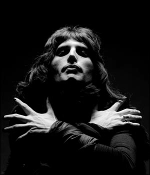 Freddie Mercury, arms across his chest, from the opening of Bohemian Rhapsody. In black and white.