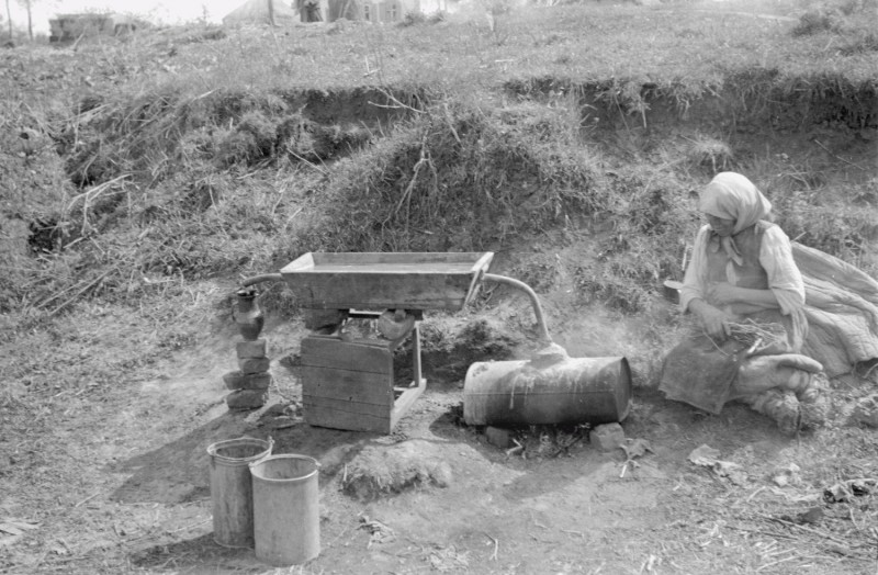 Женщина возле самогонного аппарата.