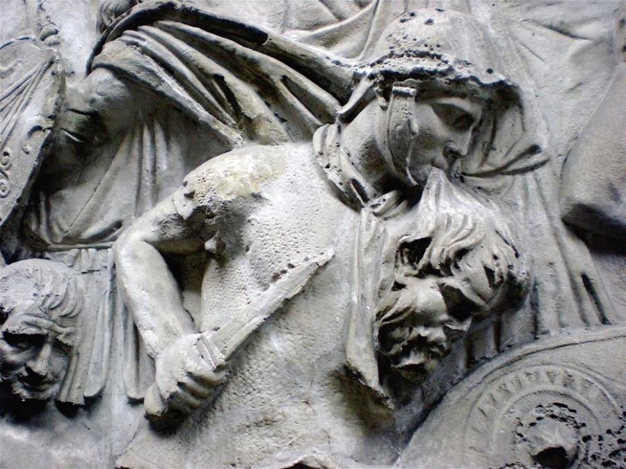 Римский воин с головой варвара в зубах на Колонне Траяна.