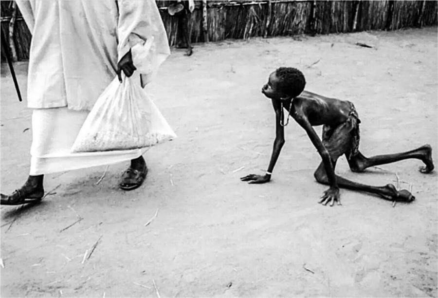 Изнеможённый от голода мальчик ползет за взрослым с мешком еды. Судан, 1998 год.