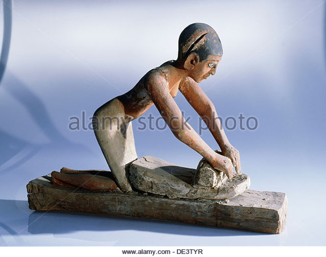Деревянная статуэтка женщины, растирающей зерно.