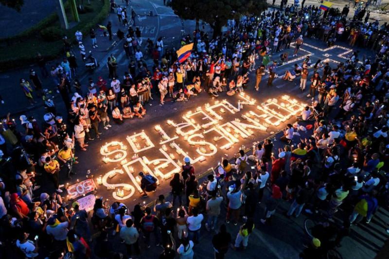 Люди собираются вокруг свечей и слов на тротуаре с надписью «За наших мертвых» во время всенощной 5 мая 2021 года в Кали, Колумбия