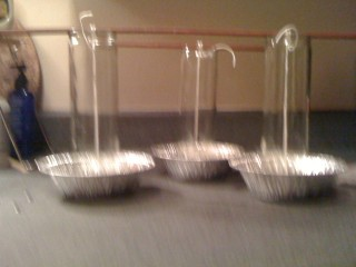 Blurry picture of three candle glasses in pie tins. Each has a wick suspended from a chopstick at the top to a grommet at the bottom.