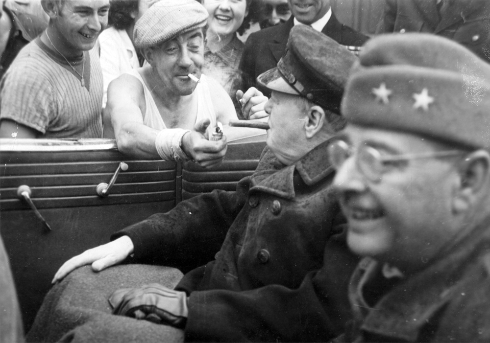 Во время проверки восстановительных работ в Шербуре,Франция, Уинстон Черчилль раскуриваетсвою сигару от огня, поданого французским рабочим.