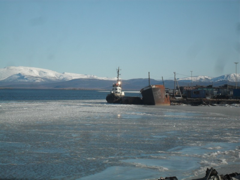 Морской буксир с наливным плашкоутом у пирса на реке Пахача Камчатский край