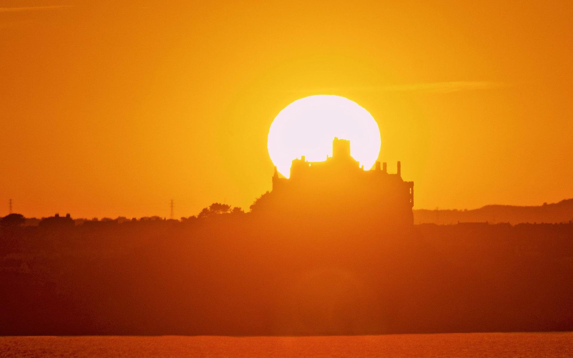 The sun rises behind St Michael's Mount, Cornwall.jpg