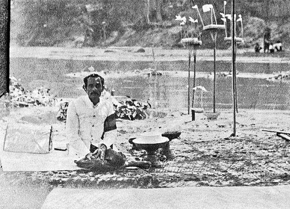 1909 A lone mourner awaits the riverside cremation ceremony of King Chao Intavarorodsuriyawong, Chiang Mai.jpg