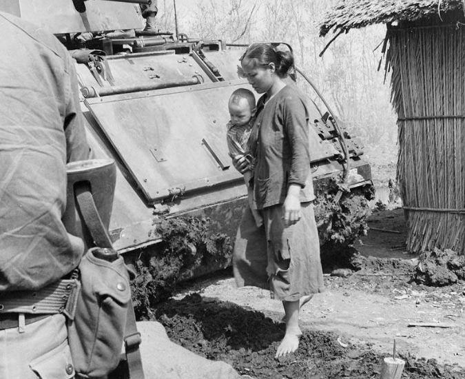1964г. Южновьетнамские солдаты ищут оружие и сжигают лишние, как они подозревают, запасы риса. Молодая женщина с ребенком не обращает внимания ни на технику, ни на фотографа...