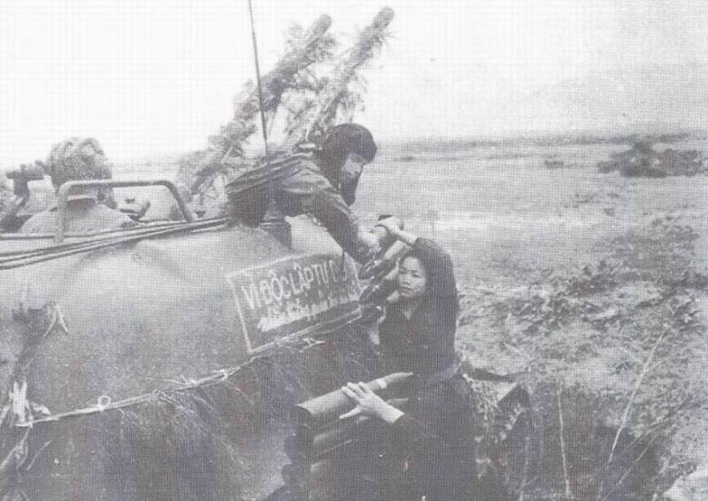 """Девушка помогает грузить снаряды в ЗСУ-57-2. Надпись на броне """"За независимость и свободу""""."""
