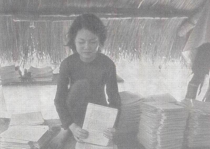 Девушка брошюрует учебники для школы.