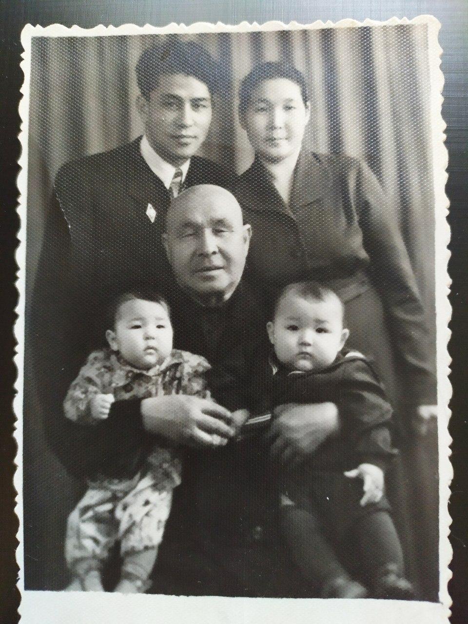 мои папа с мамой стоя, дедушка сидя, и брат с сестрой на коленях деда, 1958 год