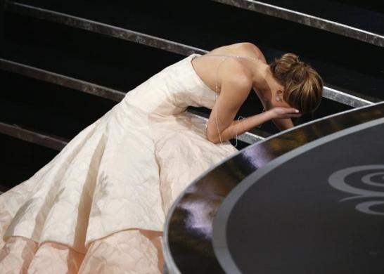 Actress Jennifer Lawrence falls as she walks up the steps to accept the award for best actress