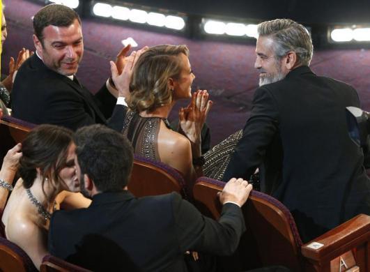 Director and producer Ben Affleck kisses his wife Jennifer Garner, as producer George Clooney, Argo