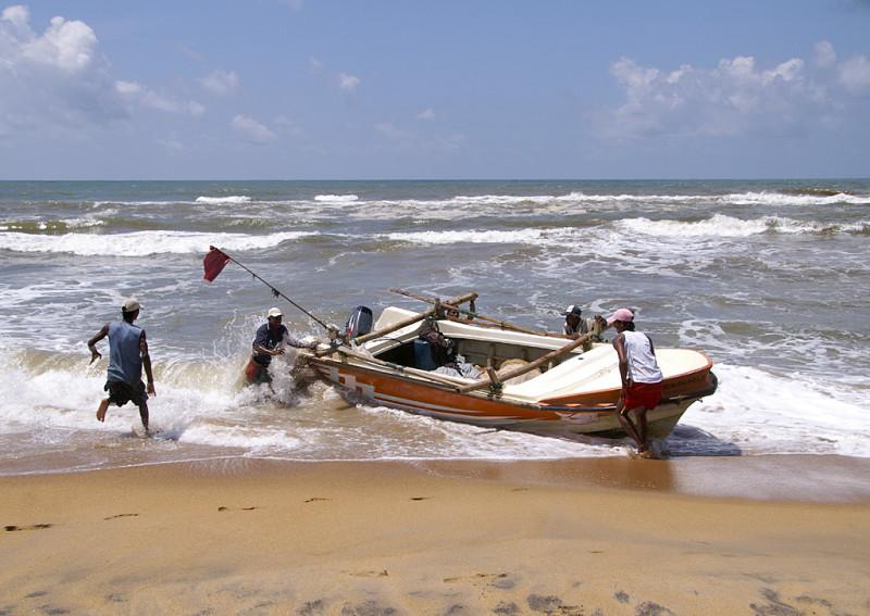 Мужики пришли с моря, пристать к берегу в прибой недостаточно: надо вытащить лодку, чтобы её не разбили волны.