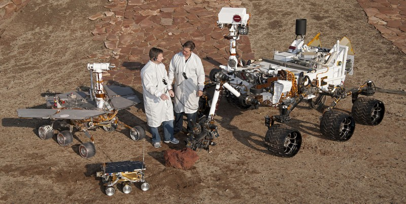 1280px-PIA15279_3rovers-stand_D2011_1215_D521