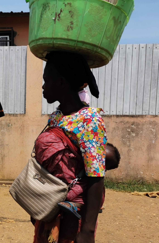 Женщина тащит малыша за спиной.