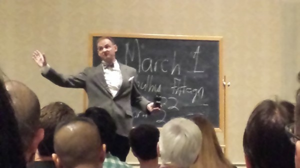 An actor in a bow tie, gesturing before a chalkboard
