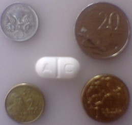 Augmentin Duo Forte pill with coins for scale