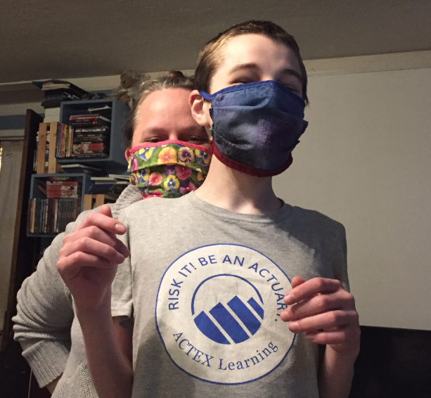 """Two people wearing fabric face masks, person in front wearing a Tshirt saying """"RISK IT! BE AN ACTUARY"""""""
