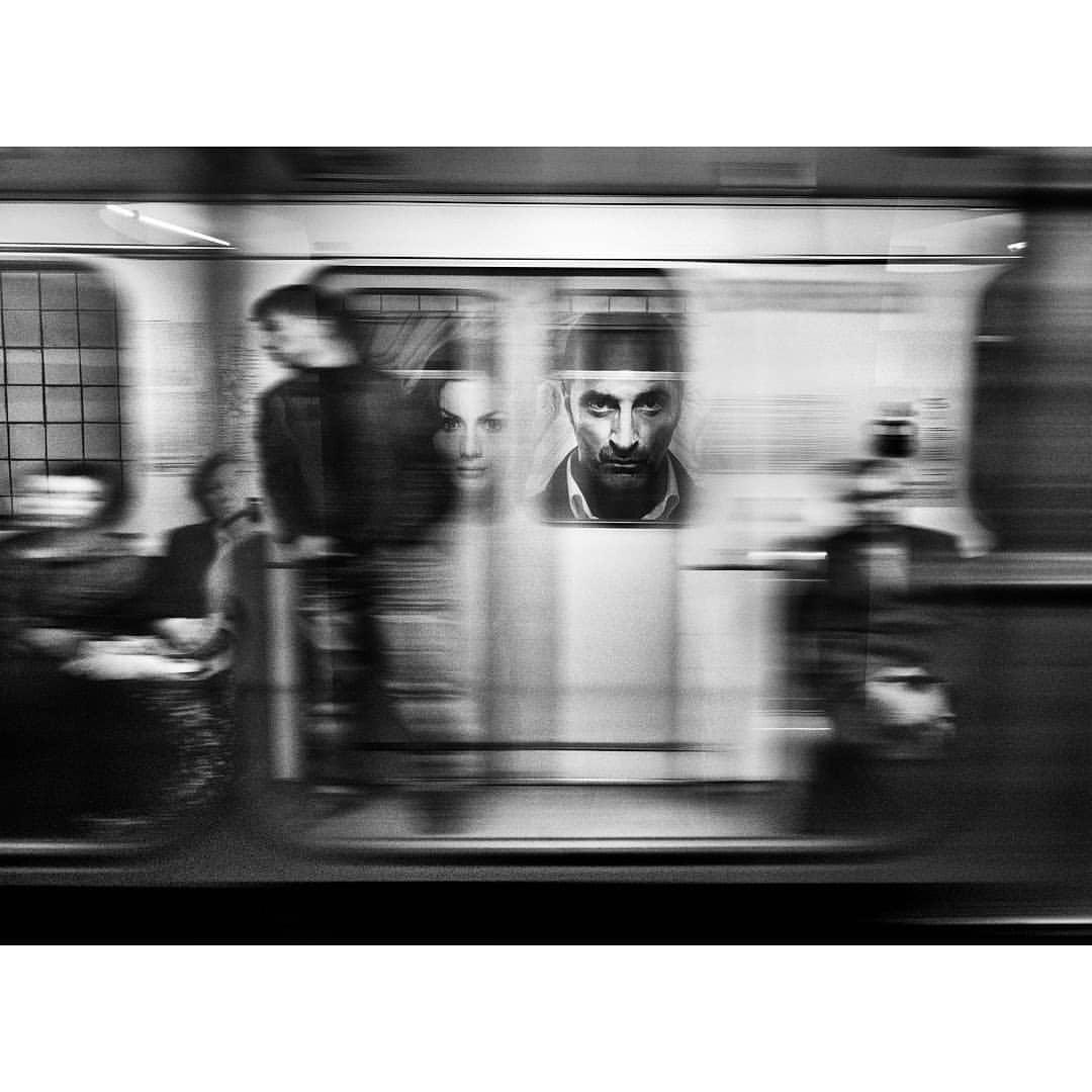"""Плакат на стене станции """"Таганская"""", и движущийся поезд перед ним"""