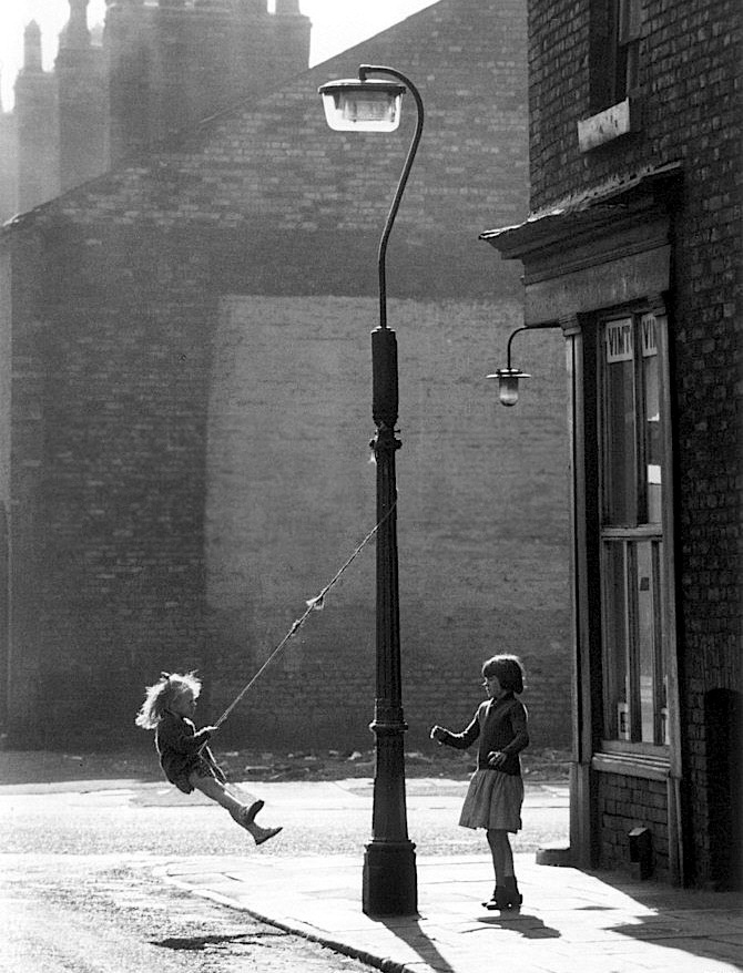 Shirley Baker, Girls swinging on a lamppost, Manchester , 1965.