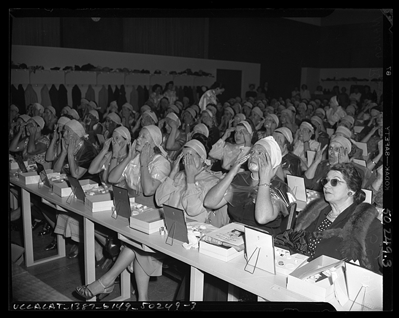 Audience applying makeup at lecture by beautician in Los Angeles, circa 1950