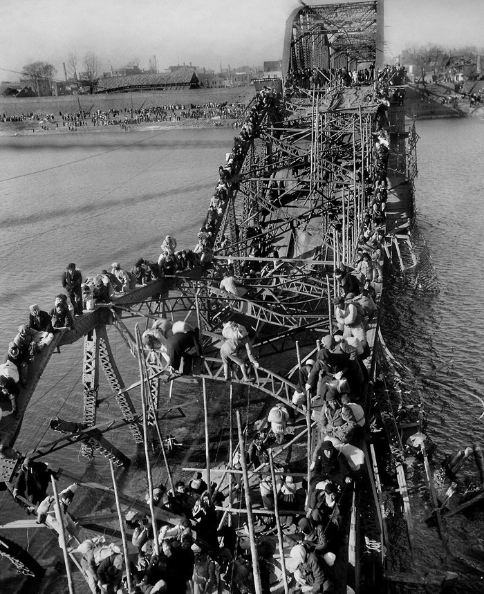 Civilians fleeing south across a destroyed bridge during the Korean War