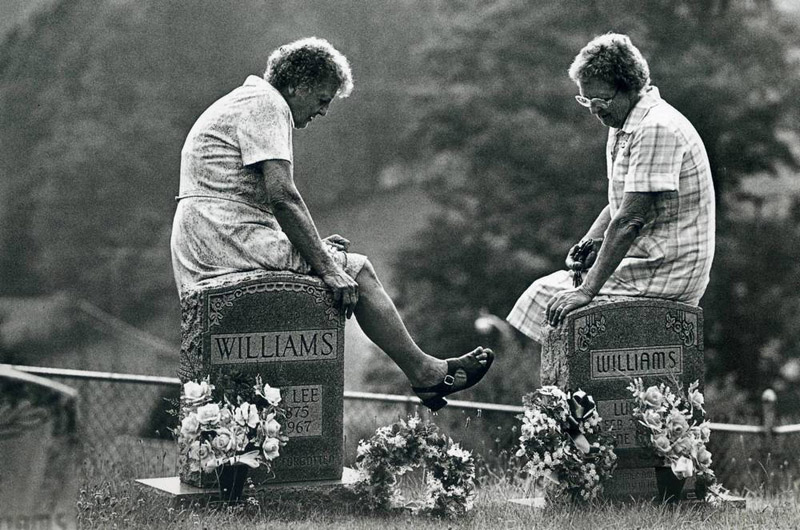 David Turnley. Two elderly women visiting the graves of their dead parents in the Appalachian Mountains sit on the headstones and talk.