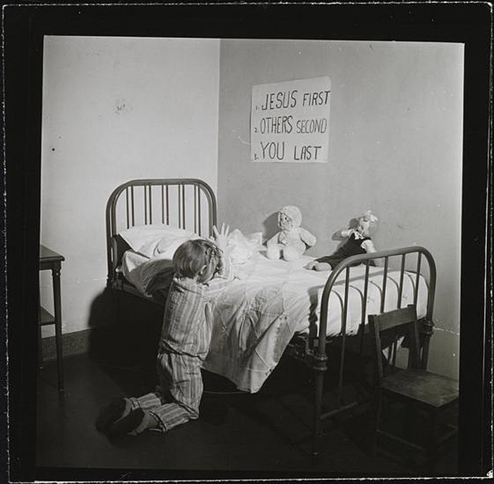 Girl praying in an orphanage, New York City, 1947
